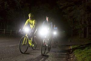 Men on road using bike light while riding bike